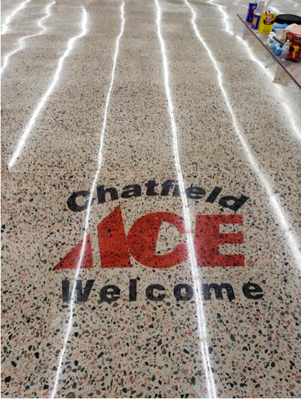 "A polished concrete floor with ACE hardware logo in red and ""Chatfield Welcome"" in black text."